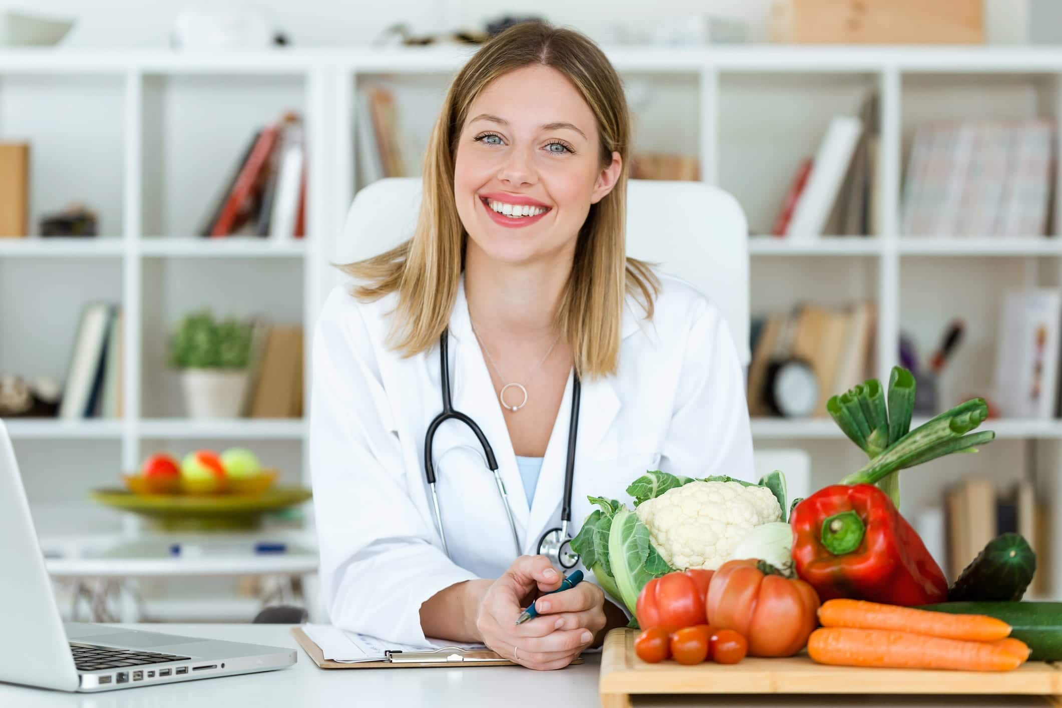 Nutrition professional at her desk with vegetables