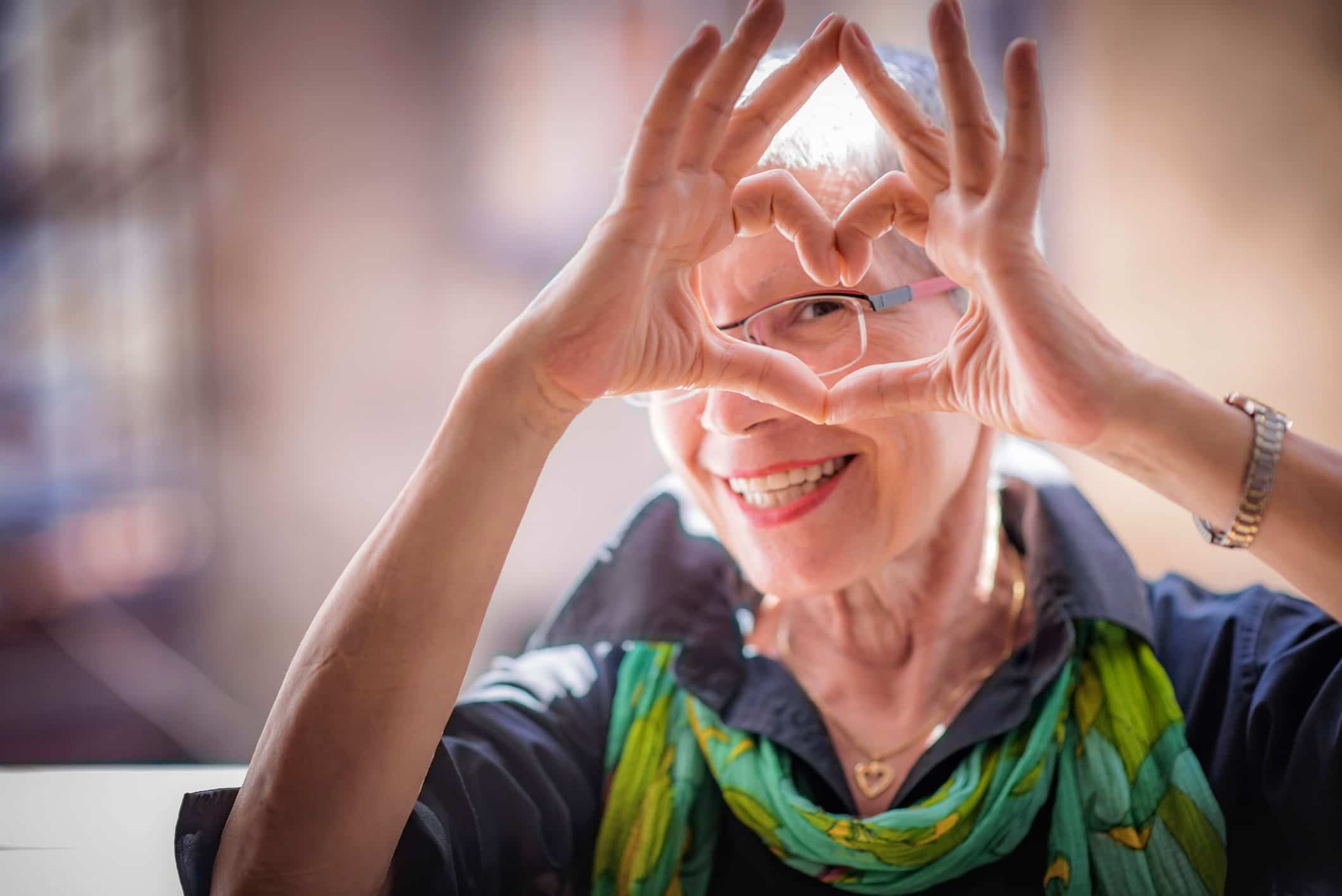 Older woman making a heart with her hands