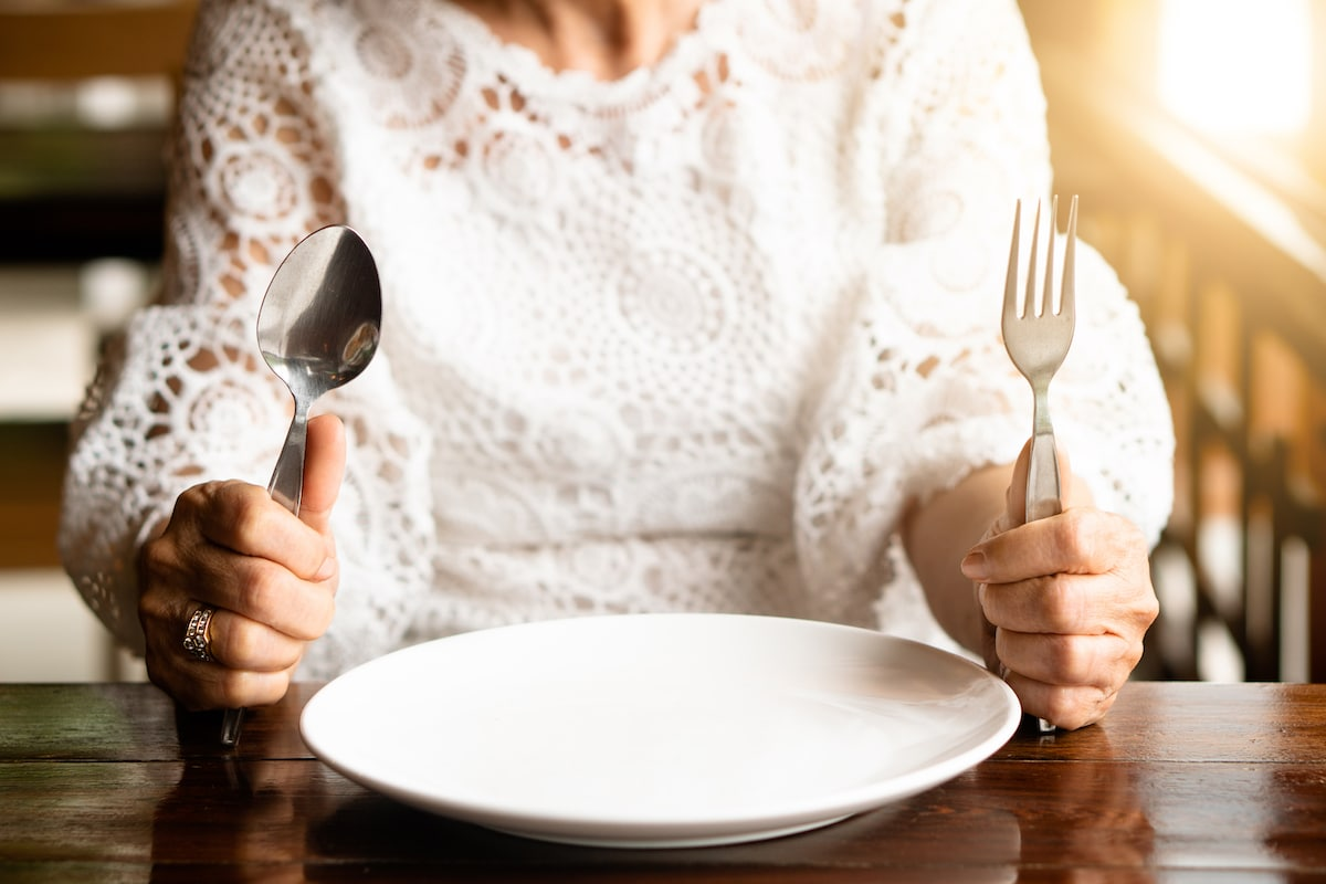 Older woman sitting at the table with an empty plate