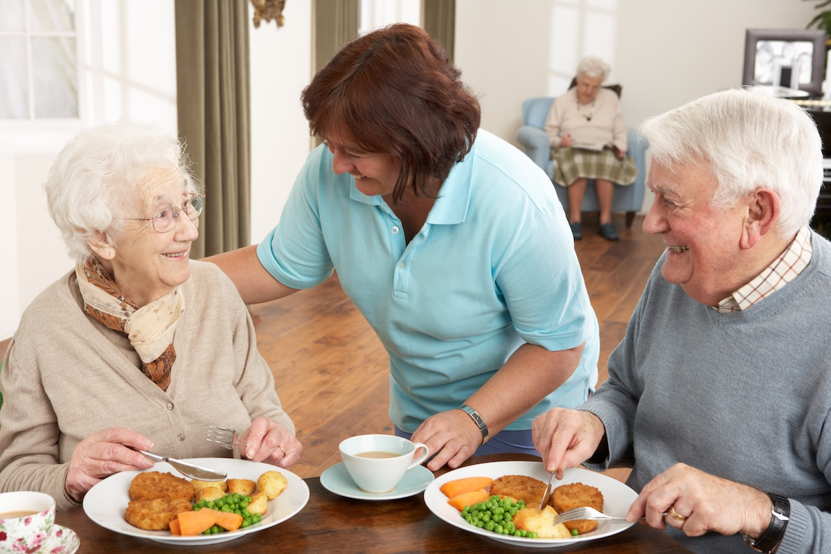 Seniors eating a healthy meal in a nursing home