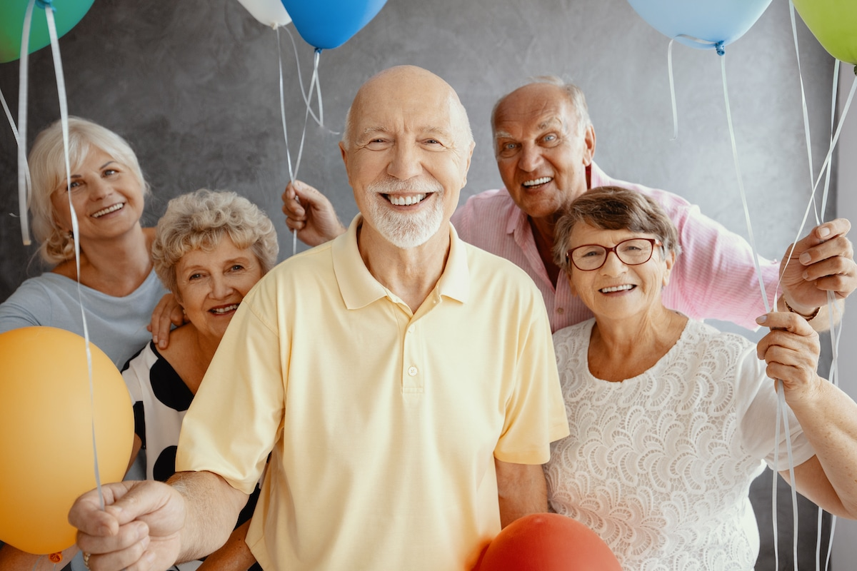 Elderly adults smiling and holding balloons