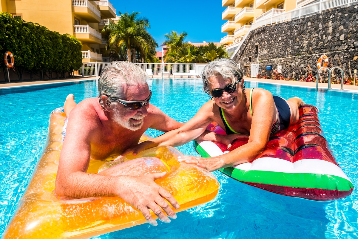Older couple lounging on rafts in the pool