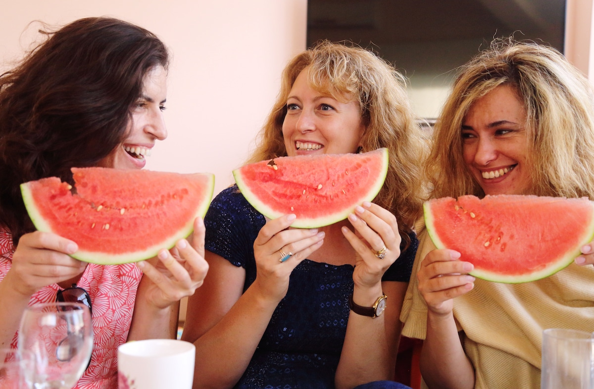 Three women eating watermelon