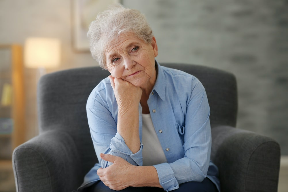 Tired elderly woman sitting in a chair