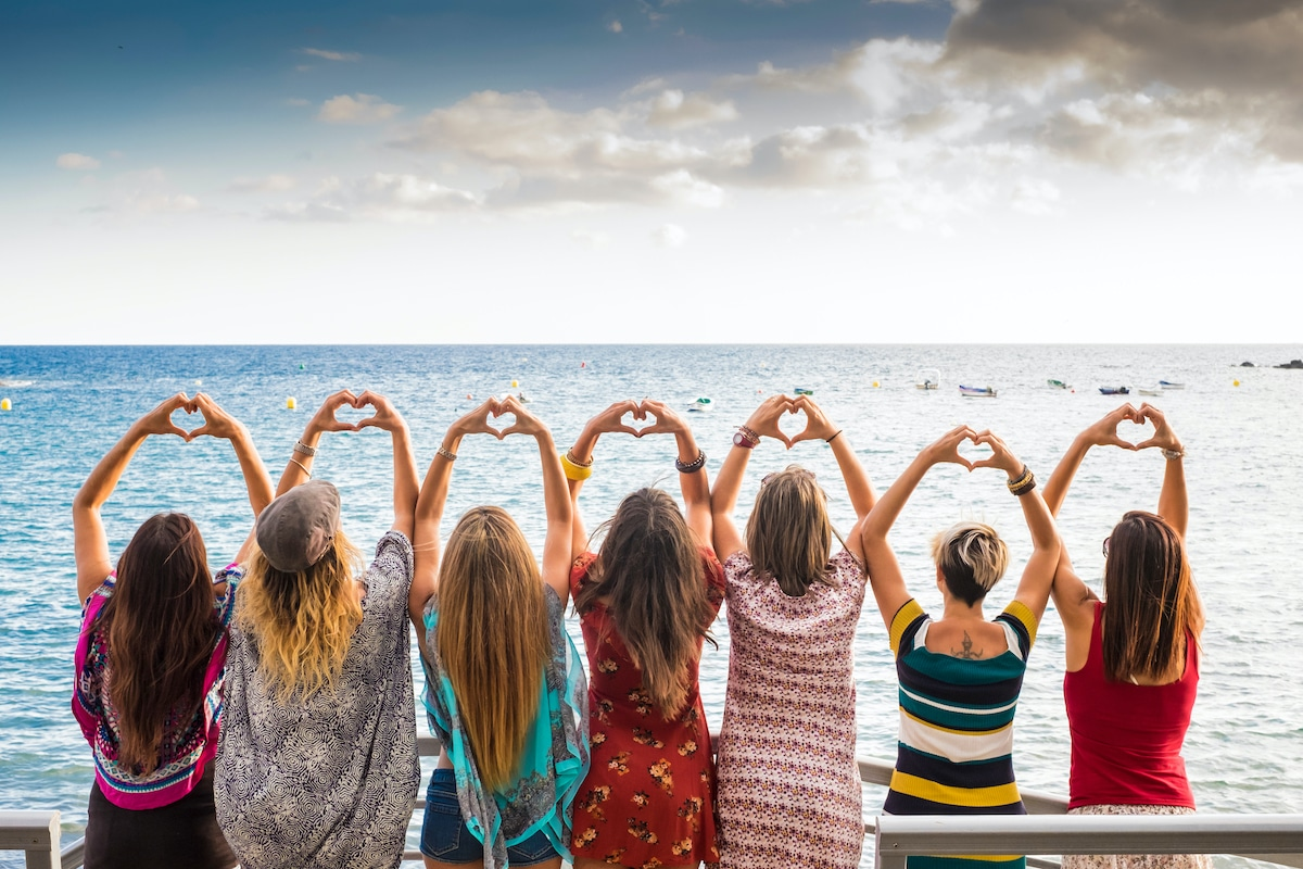 Group of girls making hearts with their hands in front of water scene