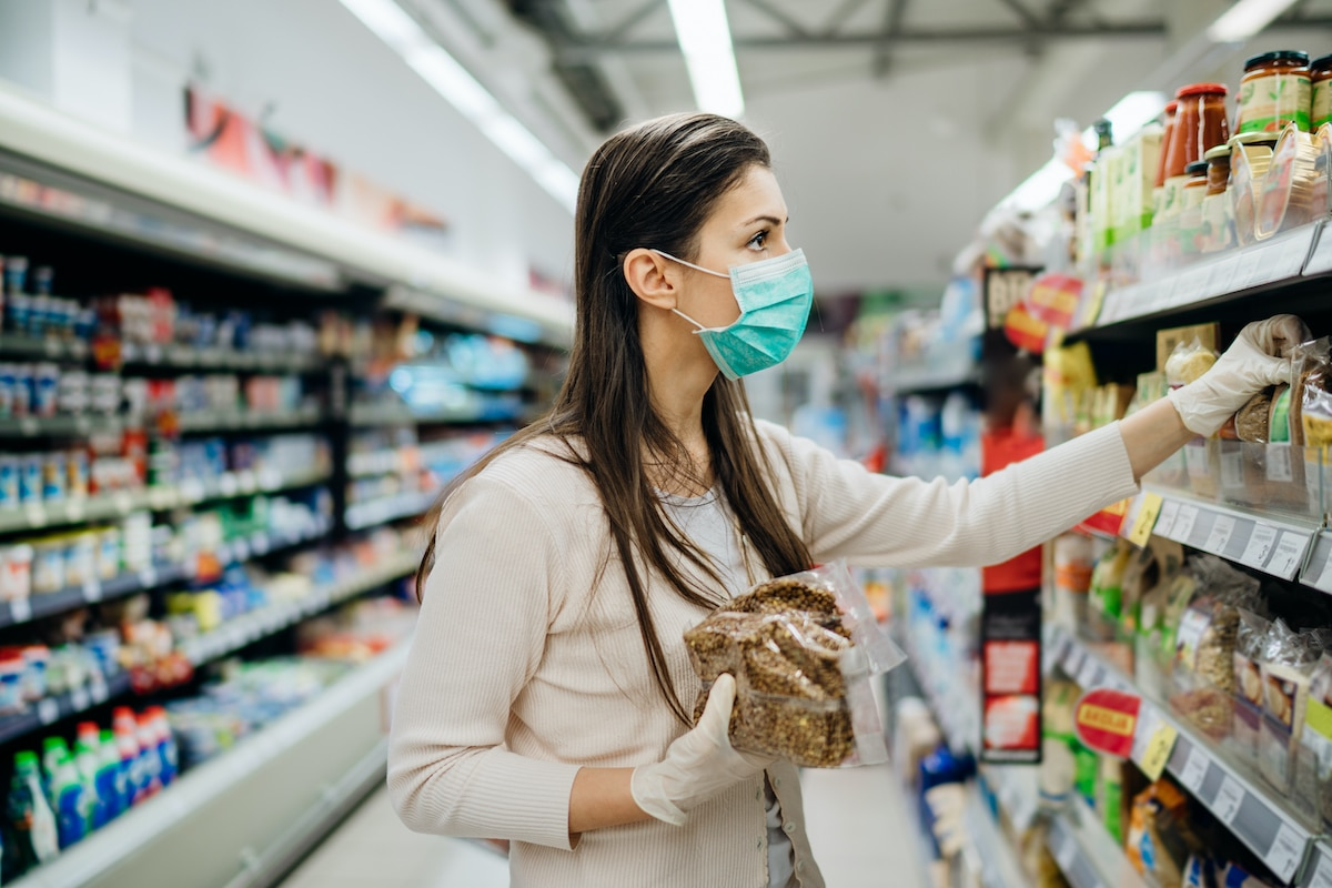 Woman wearing mask and gloves in grocery store during COVID-19 pandemic