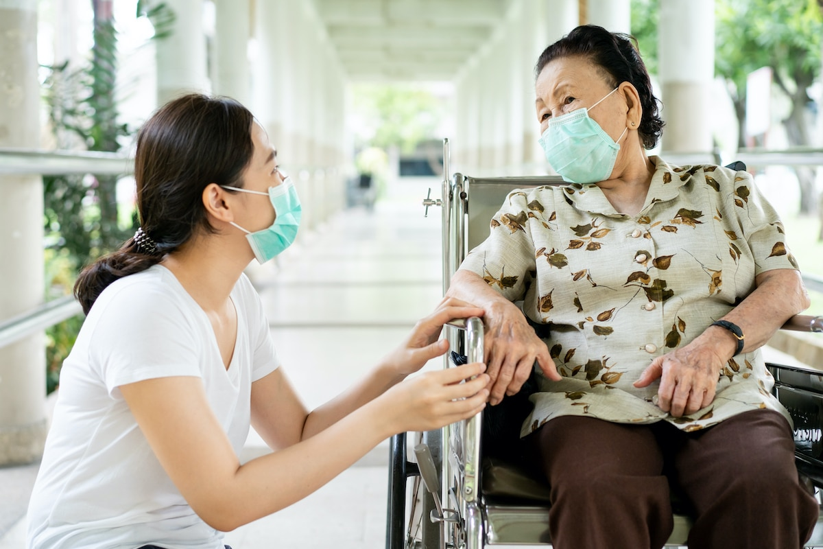 Nurse with Woman in Wheelchair both wearing masks